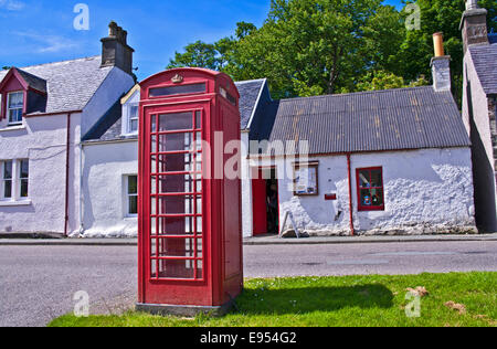 Red telephone box on village street in front of row of old traditional Scottish cottages, Plockton,, Highlands, - Stock Photo