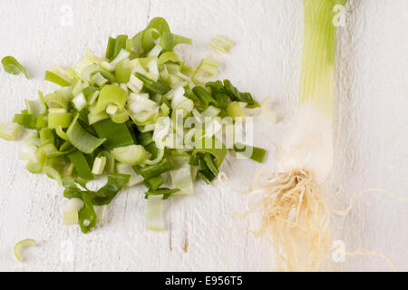 Closeup texture of a pile of diced fresh leeks with a whole one behind for use as an ingredient and vegetable in - Stock Photo