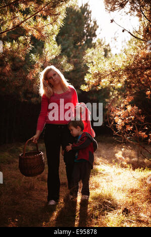 mother and her son hugging toge picking berries and mushrooms into basket in the pine wood tree forest - Stock Photo