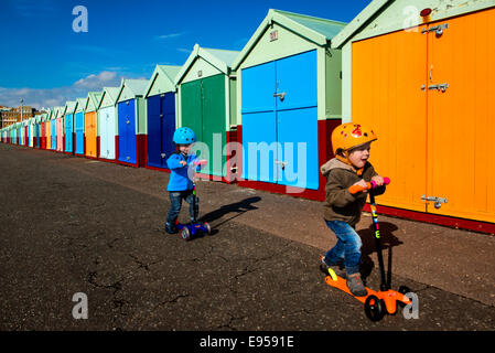 Twin boys on scooter at Brighton beach huts - Stock Photo
