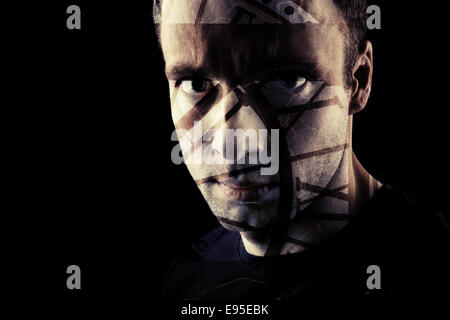 Stylized closeup portrait of a man on black, dark moody toned - Stock Photo