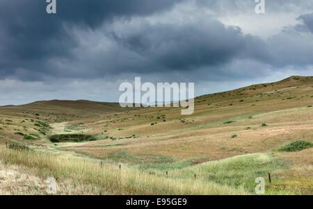 Vermilion, Nebraska, USA - Open prairie, grassland, and dry scrub and hills under a threating  sky near Vermilion, - Stock Photo