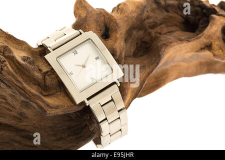 A mans wrist watch on a piece of fossilised wood - studio shot with a white background - Stock Photo