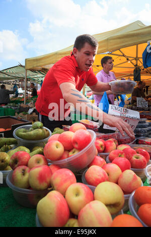 Busy market trader selling fruit off a market stall - Stock Photo