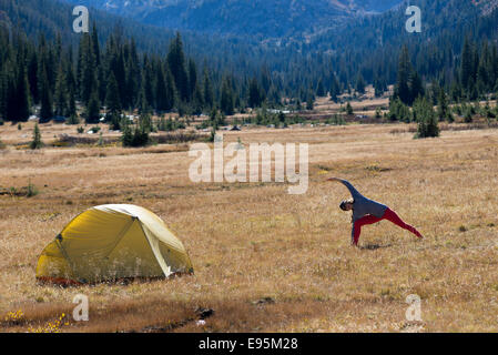 Woman doing yoga at her camp on a backpack trip in Oregon's Wallowa Mountains. - Stock Photo