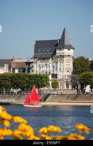 In Summer, a small red sailing boat on the Allier Lake (Vichy). Petit voilier à voiles rouges sur le Lac d'Allier, - Stock Photo