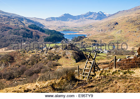 Ladder stile on footpath above Capel Curig with view to Nantygwryd and Snowdon Horseshoe in Snowdonia National Park - Stock Photo