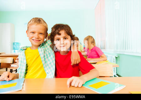 Two boys hugging and sitting together in classroom - Stock Photo