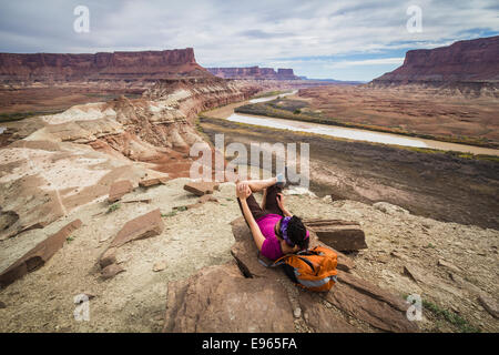 Hiker on the trail to Fort Bottom ruins from the White Rim trail near Moab, Utah. Canyonlands National Park. - Stock Photo