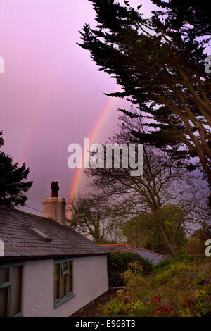 Double rainbows over a welsh long cottage as the sky turns pink with the closing weather over rural Flintshire in - Stock Photo