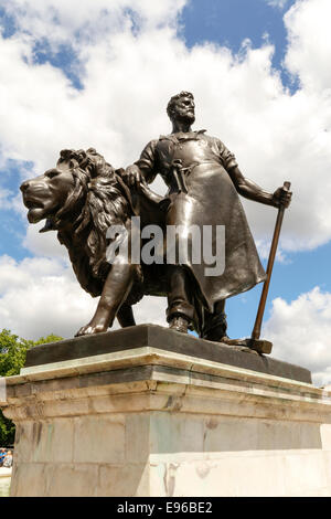 Bronze statue of man with lion, part of Queen Victoria Memorial outside Buckingham Palace, London - Stock Photo