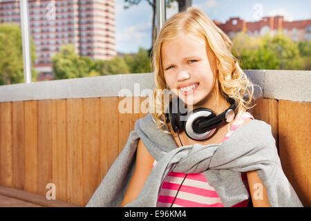 Close view of girl wearing headphones, sweatshirt - Stock Photo