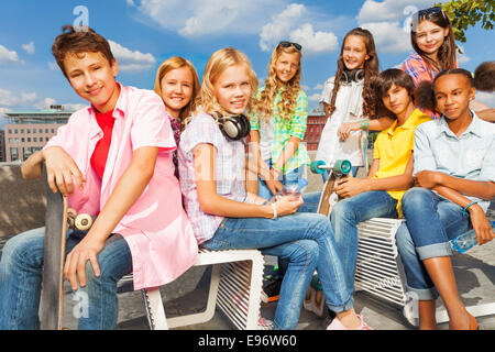 Group of kids sit on white chairs with skateboards - Stock Photo
