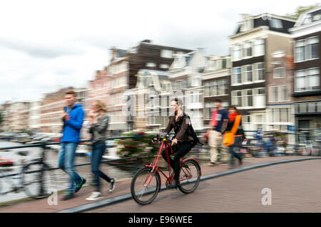 Young woman riding bicycle in Amsterdam Netherlands (Holland) Europe - Stock Photo