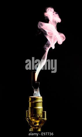 Broken lightbulb flares up in smoke - Stock Photo