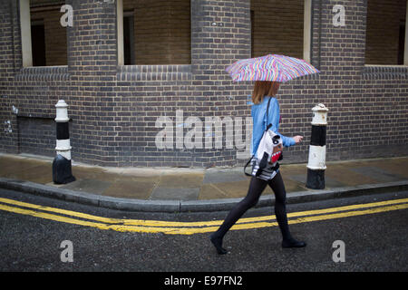 Woman walks past a wall within a wall in Spitalfields, East London. A building being renovated / preserved proves - Stock Photo