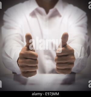 Man with two thumbs up at the background of a glossy table, concept image for illustration of excellence or best - Stock Photo