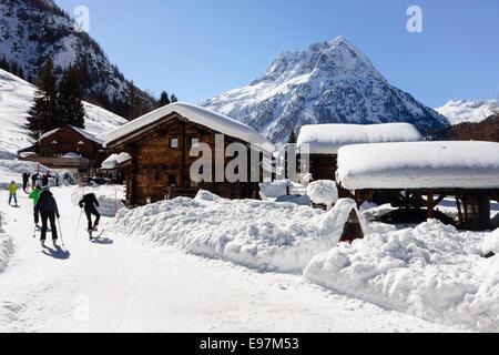 Skiers on snow slope approaching small Alpine village of Vallorcine in Chamonix valley, Haute Savoie, Rhone-Alpes, - Stock Photo