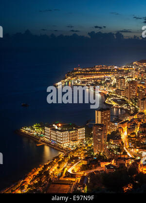 Aerial view over the city and port of Monte Carlo, Monaco along the French Riviera at night, Côte d'Azur - Stock Photo