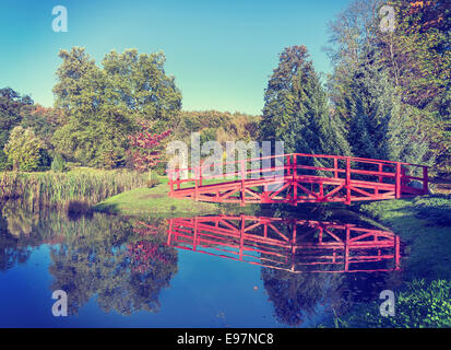 Vintage retro filtered picture of red bridge in garden. - Stock Photo