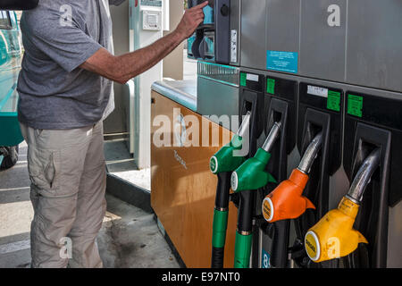 Man selecting fuel pump at Total gas station for refueling his car - Stock Photo