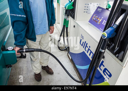 Man pumping fuel into his vehicle at BP service station - Stock Photo