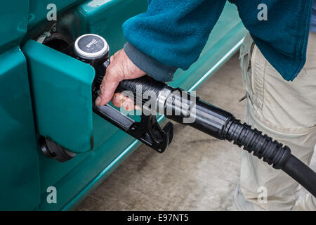 Close up of man pumping diesel fuel into his vehicle at service station - Stock Photo
