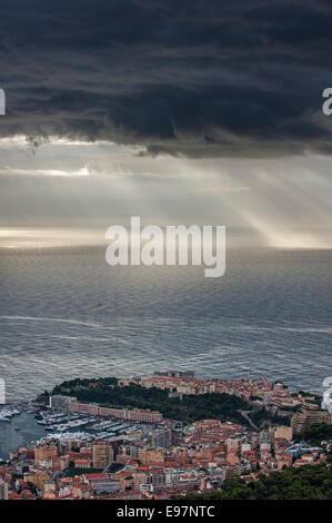 Aerial view over the city and port of Monte Carlo, Monaco and dark menacing rain clouds over the sea along the French - Stock Photo