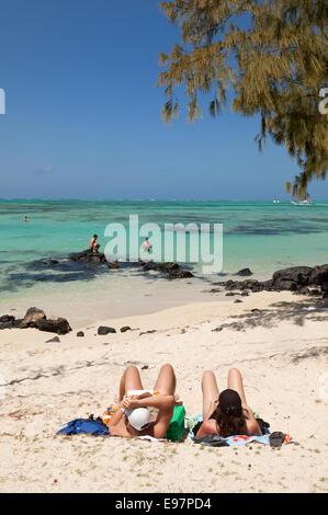 A couple sunbathing on a tropical beach, Ile Aux Cerfs island, east coast, Mauritius - Stock Photo
