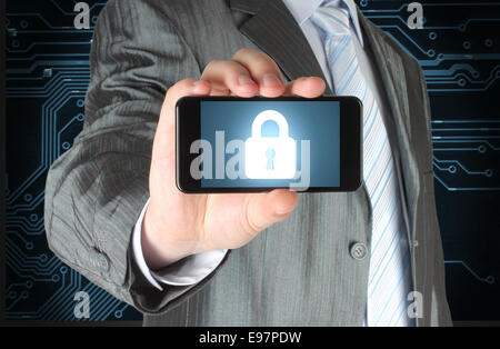Businessman holds smart phone with closed lock on circuit board background, security concept - Stock Photo