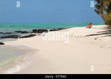 A couple on the white sand beach, Ile aux Cerfs island, east coast, Mauritius Africa - Stock Photo