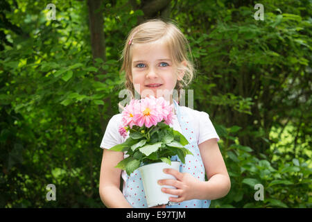 Girl gardening, holding pot with flowers - Stock Photo