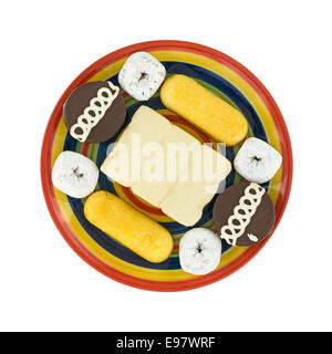 Top view of junk food including powdered donuts, cream filled cakes, chocolate iced cakes and iced covered cakes - Stock Photo