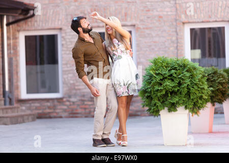 Happy young couple fooling around outdoors - Stock Photo
