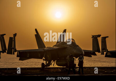 A US Navy F/A-18E Super Hornet fighter aircraft is silhouetted by the setting sun on the flight deck of the aircraft - Stock Photo