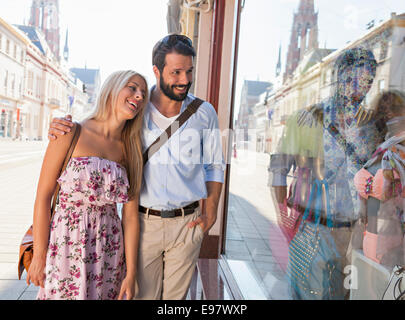 Young couple looking in fashion shop window - Stock Photo
