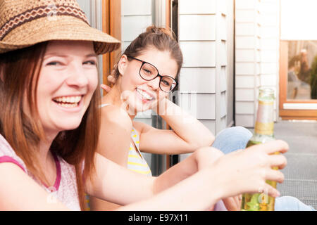 Two young women drinking beer on balcony, Munich, Bavaria, Germany