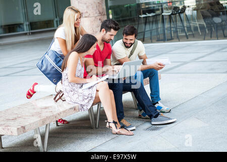 Group of students working together on laptop - Stock Photo