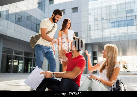 Male students shaking hands on campus grounds - Stock Photo