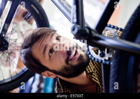 Man in bicycle shop looking at bike - Stock Photo