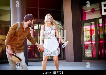 Happy young couple takes a walk in town having fun - Stock Photo