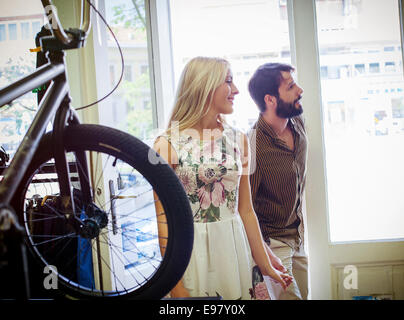 Young couple in a bicycle shop - Stock Photo