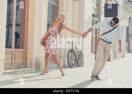 Happy young couple fooling around in town - Stock Photo