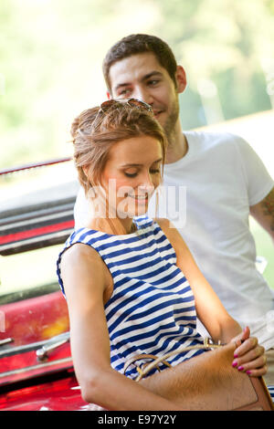 Young couple takes a break on road trip waiting by car - Stock Photo