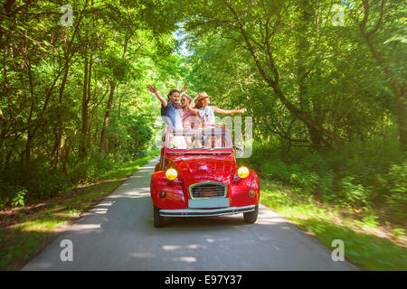 Young people in red vintage car having fun - Stock Photo