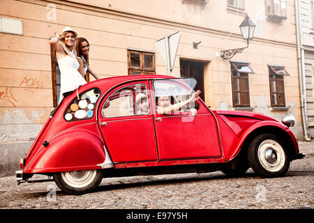 Young people in vintage car driving through town - Stock Photo