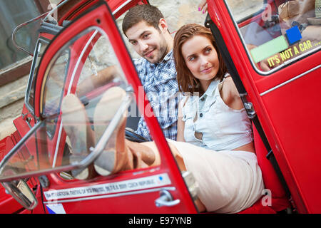 Young couple in vintage car taking a break - Stock Photo