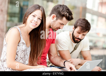 Group of university students using laptop together - Stock Photo