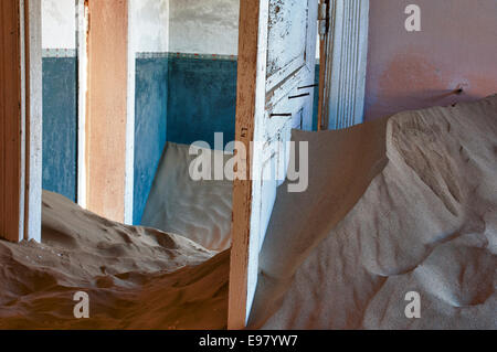 Open doors in a room full of sand in Kolmanskop, a ghost mining town in Namibia, Africa. The desert has reclaimed - Stock Photo