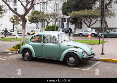 Green Volkswagen Beetle with damaged and rusty wheel arch in Barranco, Lima, Peru - Stock Photo